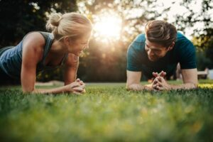 Fit young man and woman exercising in park. Smiling caucasian couple doing core workout on grass.