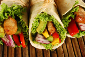 Marinated chicken with avocado wrap sandwiches on wooden woven mat